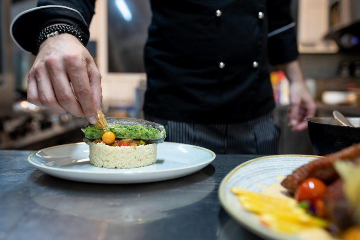 Bucătar chef aranjând un preparat din pește în bucătaria unui restaurant internațional în Sibiu