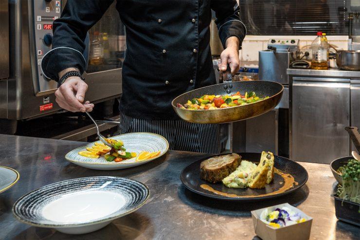 Bucătar chef gătind în bucătăria unui restaurant internațional în Sibiu